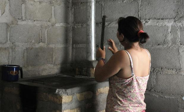 She is demonstrating one of the maintenance steps to show she understands how to maintain the stove.