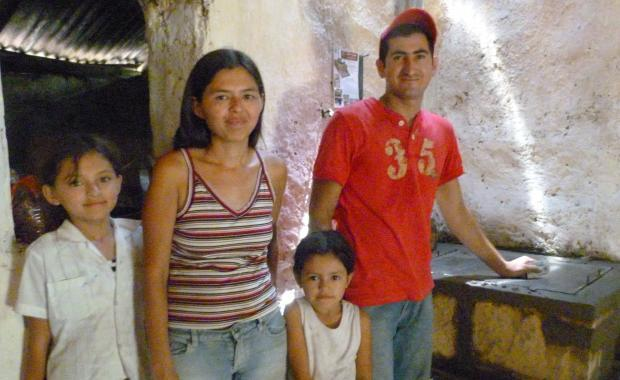 Tecnico Kelvin has finished stove construction, given a maintenance demo to the family and put the cinco on the wall behind him.