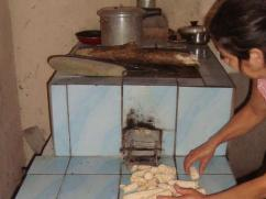 She is drying wood on top of the stove and using corncobs to start her fire.