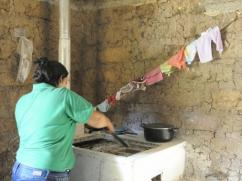 Supervisor Sindy mixing the wood ash inside the stove.